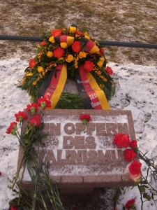 Hinter dem Stein Gedenken, ein Kranz von der Stiftung Aufarbeitung - Vor dem Stein die Alibi-Nelken der Kommunismus-Fans