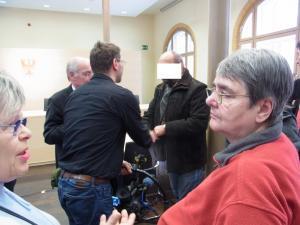 Nach der mündlichen Verhandlung wurde der Beschwerdeführer (Mitte) interviewt – Foto: LyrAg